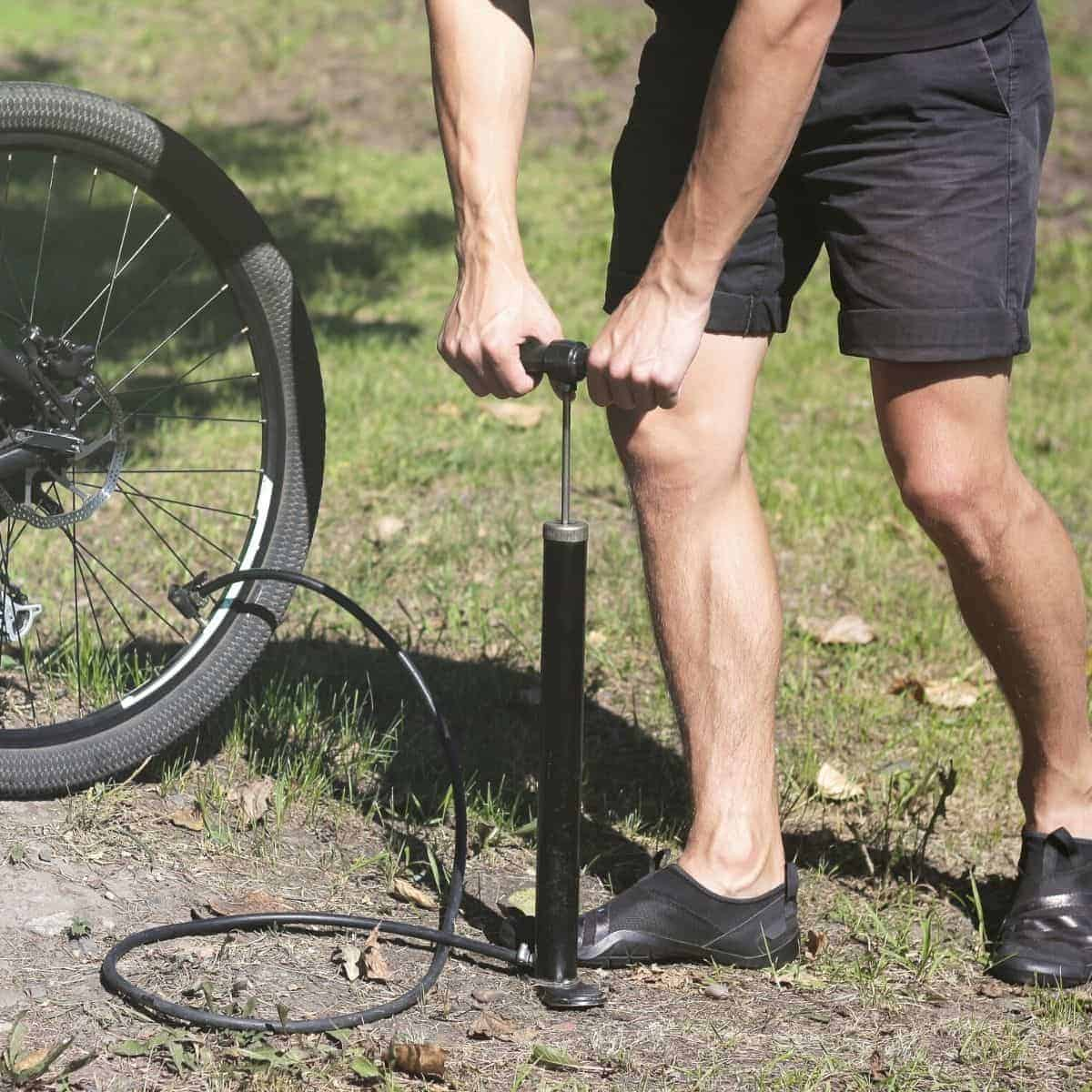 Person standing on grass and using a bike pump.