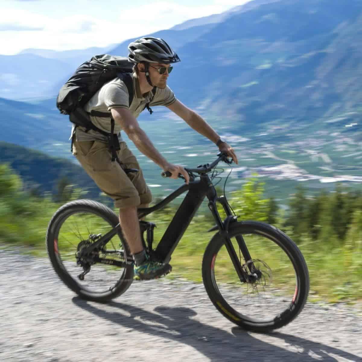 Person riding an electric bike on a mountain trail.