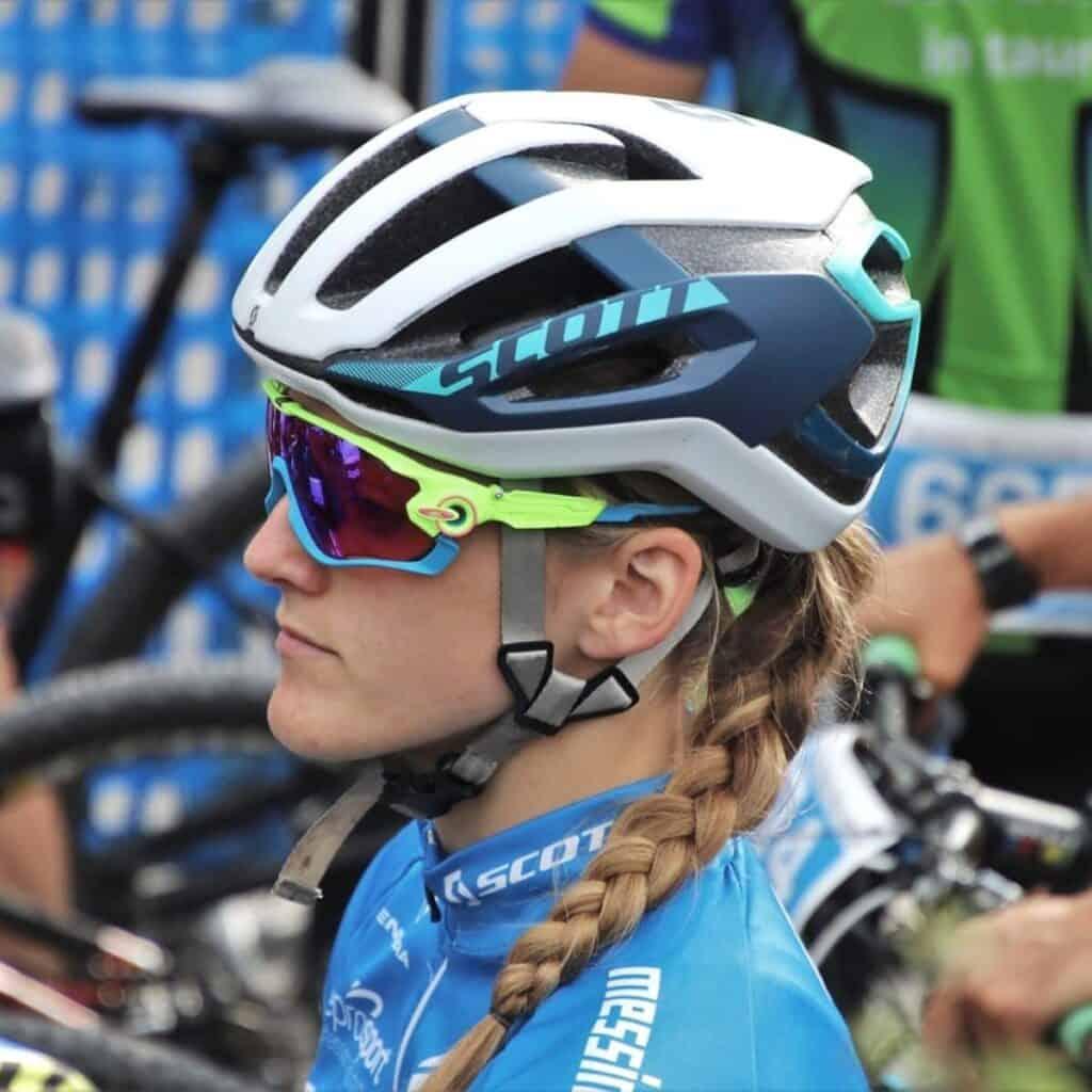 Side profile of a cyclist wearing a helmet.