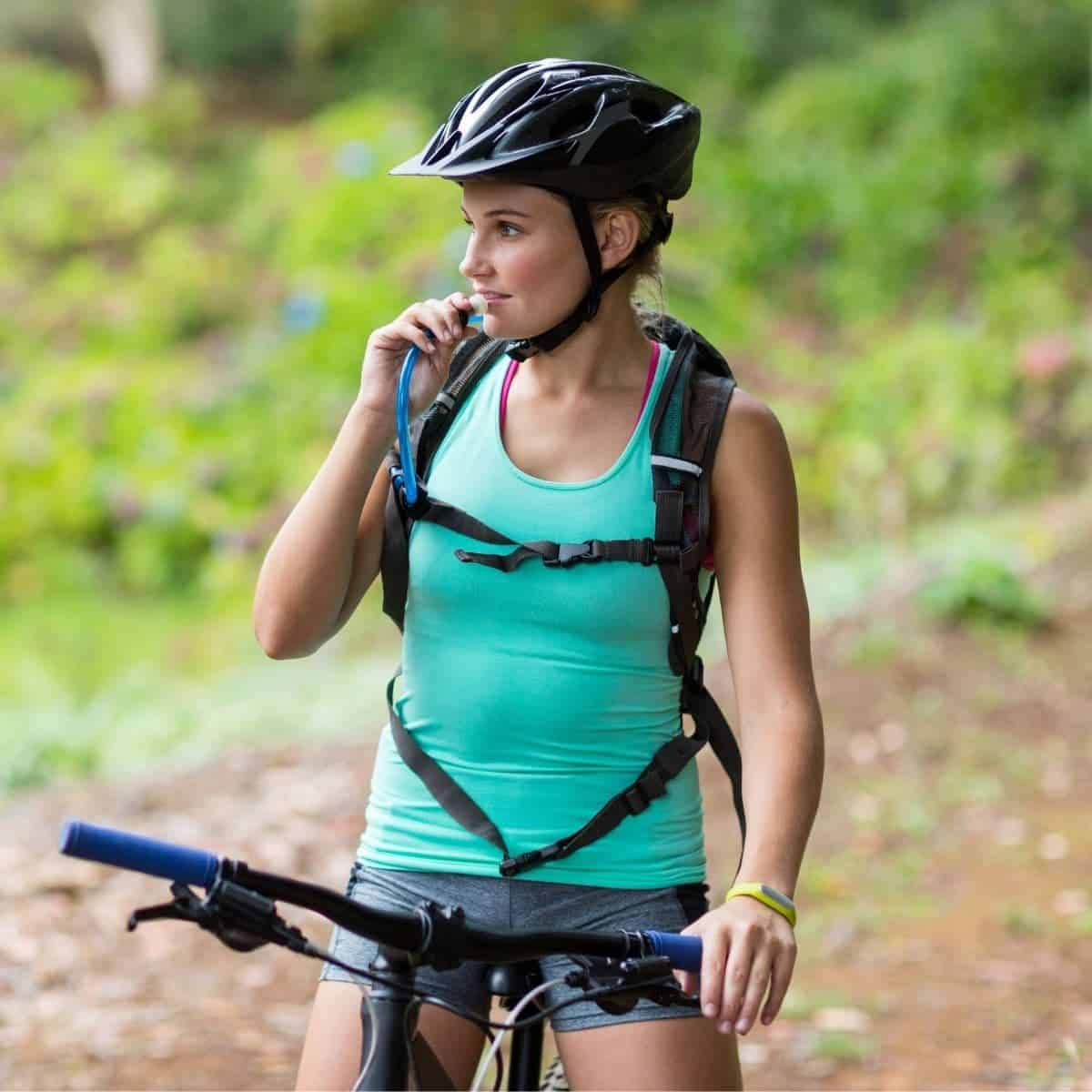 Woman on a bicycle and drinking from a hydration pack.