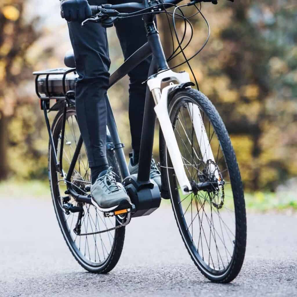 Lower half of a person riding an electric bike.