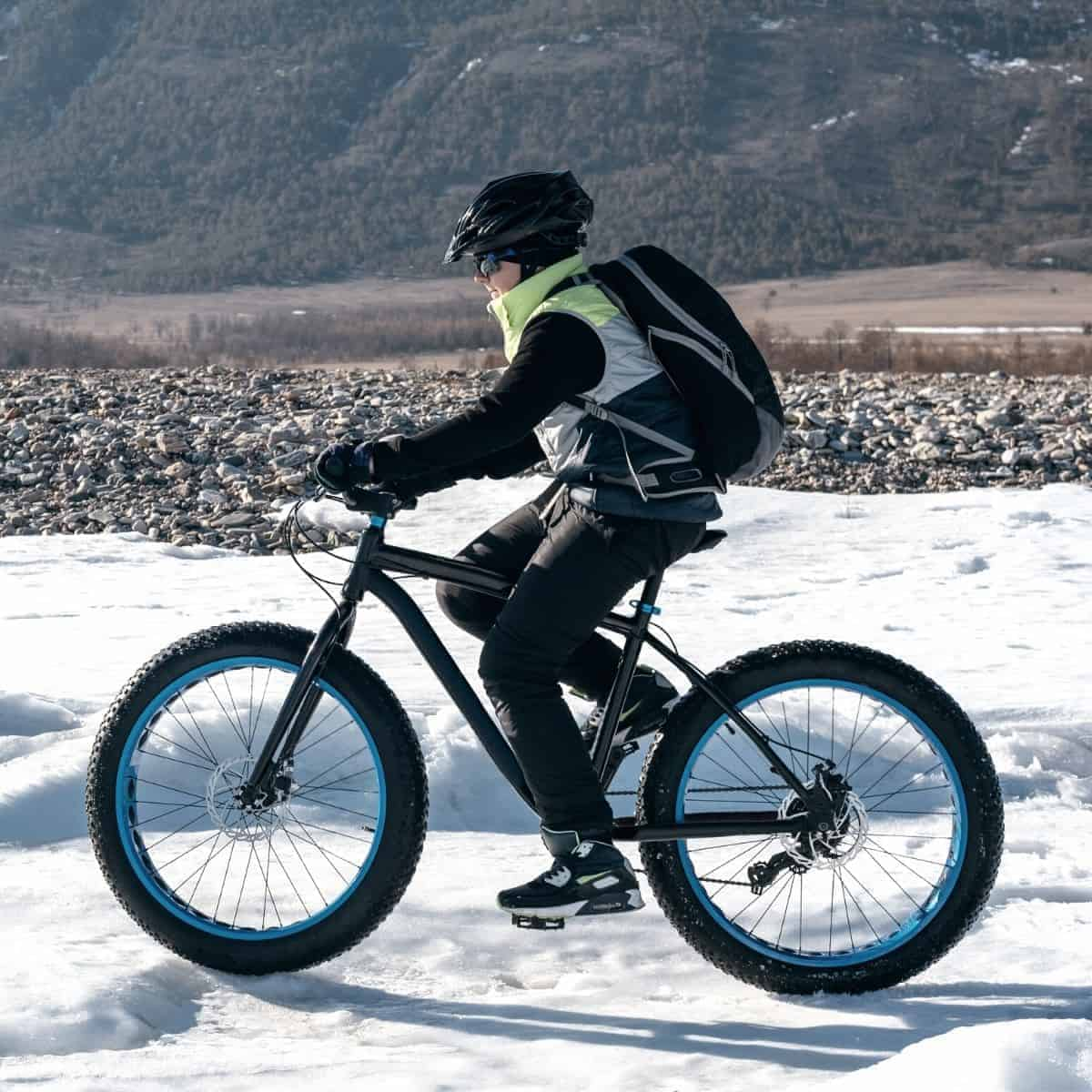 Person riding a fat tire electric bike in the snow.