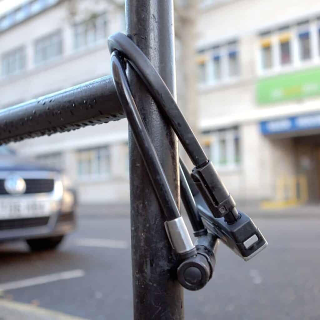 Two bike locks on a pole.