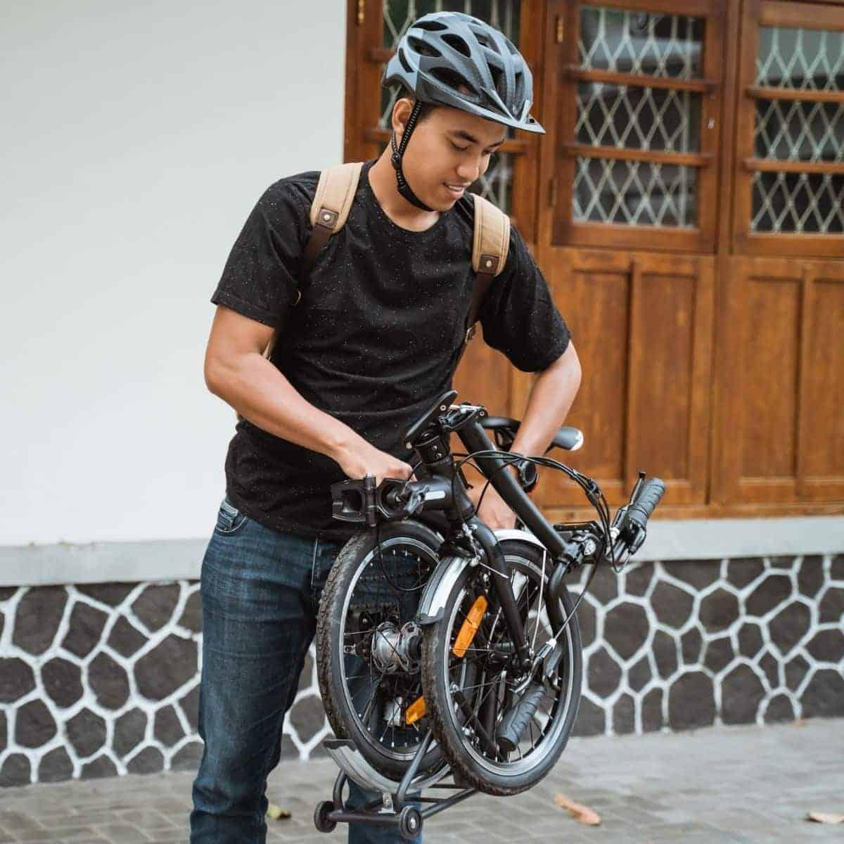 Person on a sidewalk holding a folded bike.