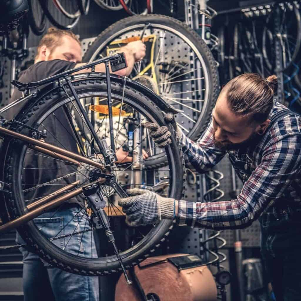 Person repairing a bicycle in a shop.